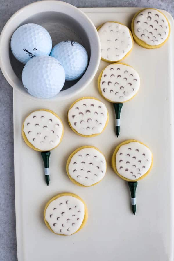 golf ball cookies finished sugar cookies on a white plate with bowl of golf balls