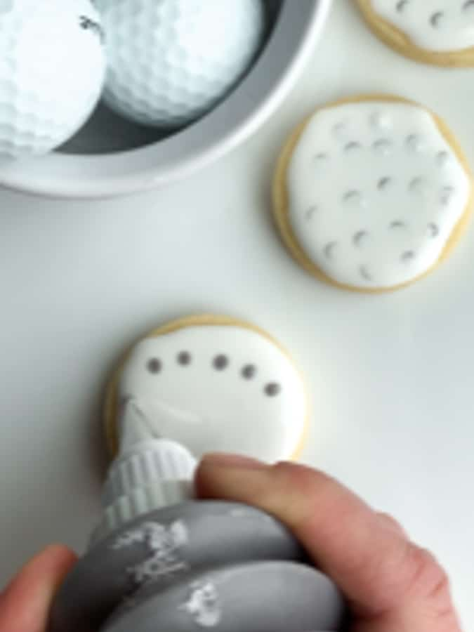 Add gray circles to the wet white icing on golf cookies