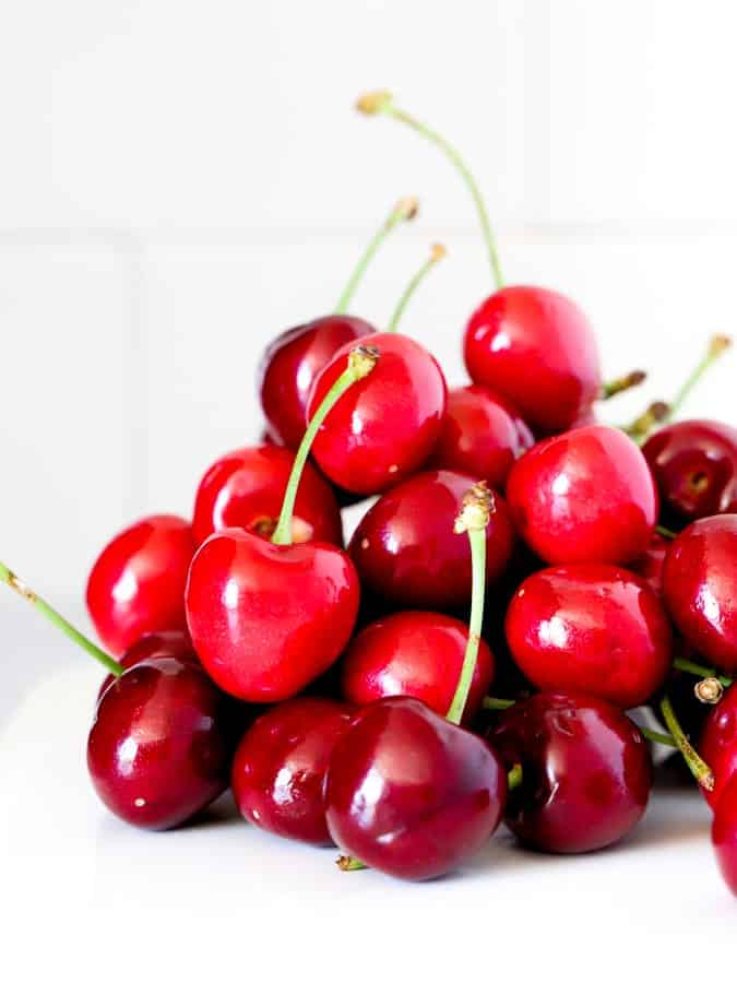 Fresh cherries in a pile on a white plate and white tile background