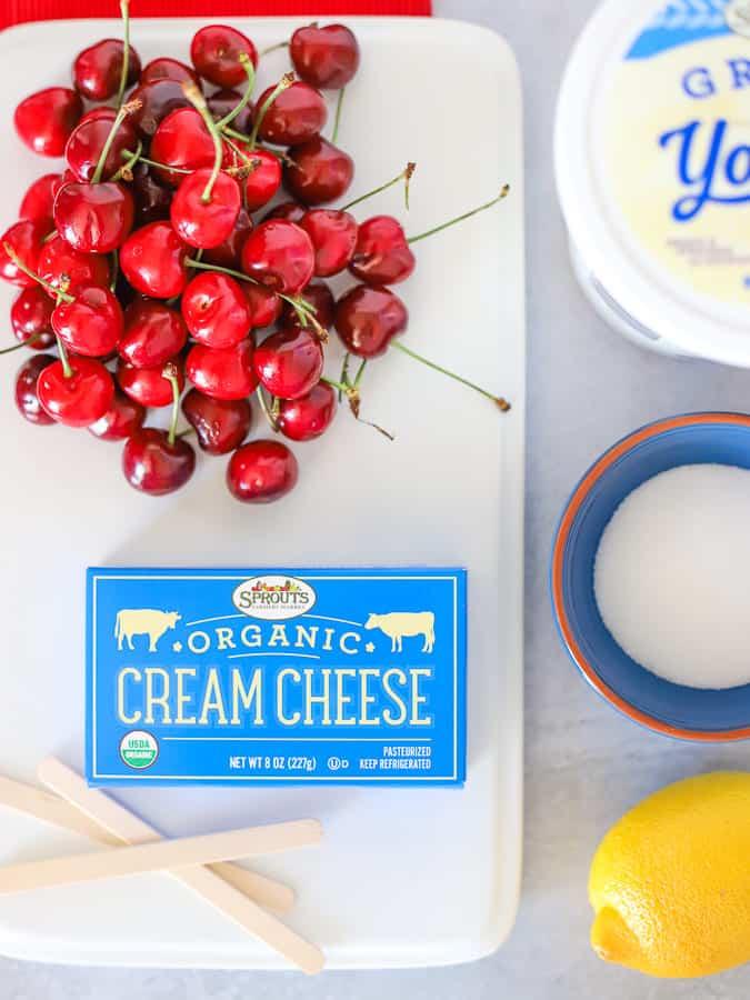 Ingredients in cherry cheesecake popsicles are cherries, cream cheese, Greek yogurt, sugar and lemon juice