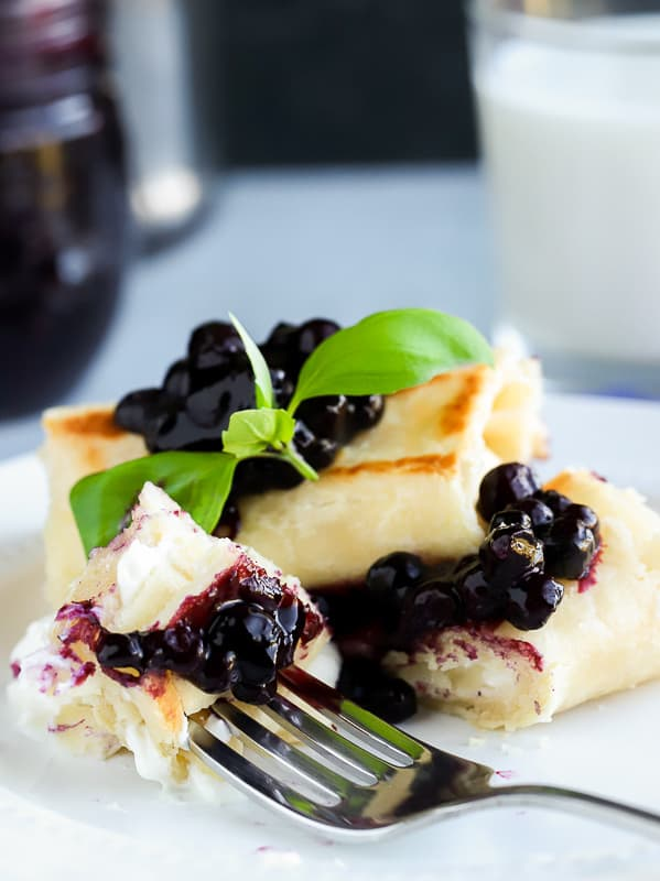Two blueberry blintz with Greek yogurt filling on a white plate with fork