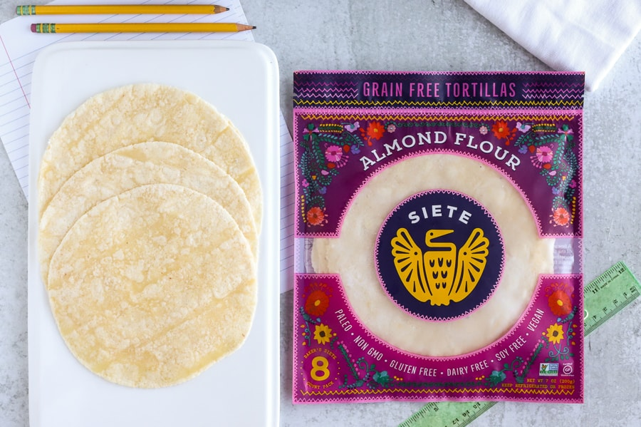 Siete Family foods almond flour tortillas on a white plate next to package