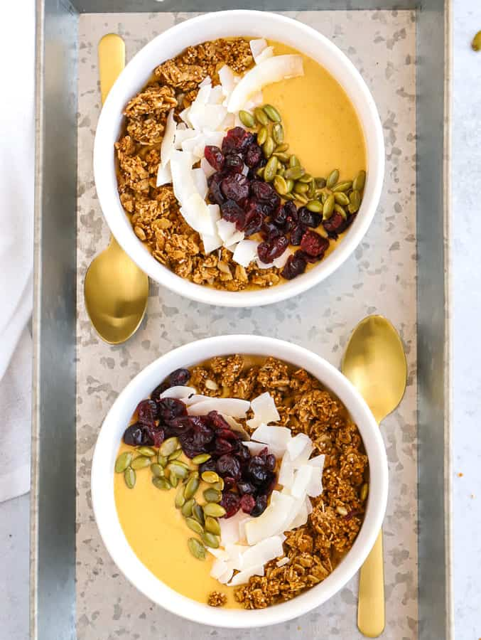 two bowls of pumpkin smoothie with granola, coconut chips, and pepitas