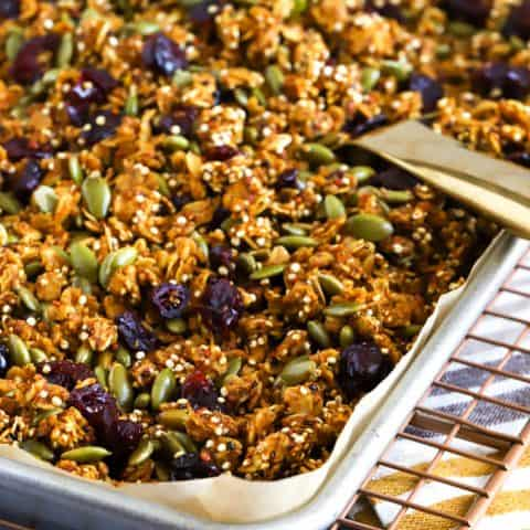 A baking tray filled with pumpkin granola and a serving spoon