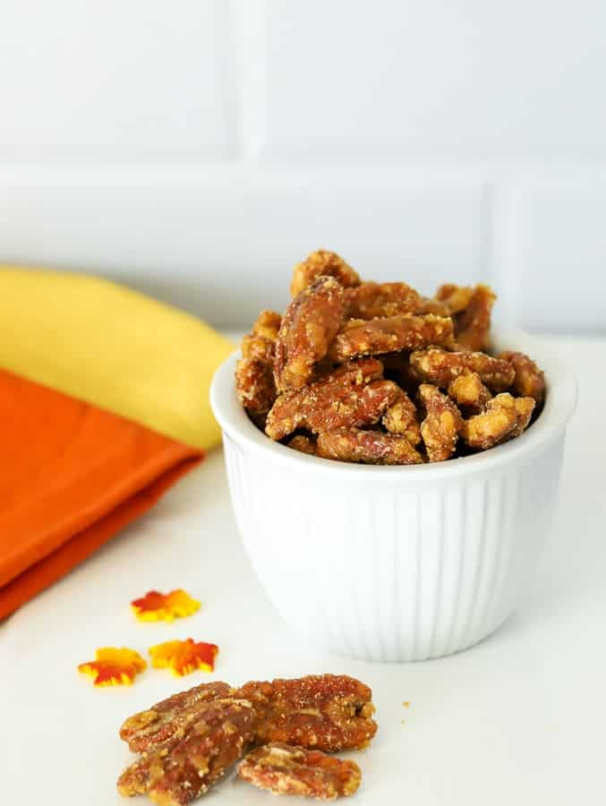 Maple candied pecans in white bowl with orange and yellow napkins
