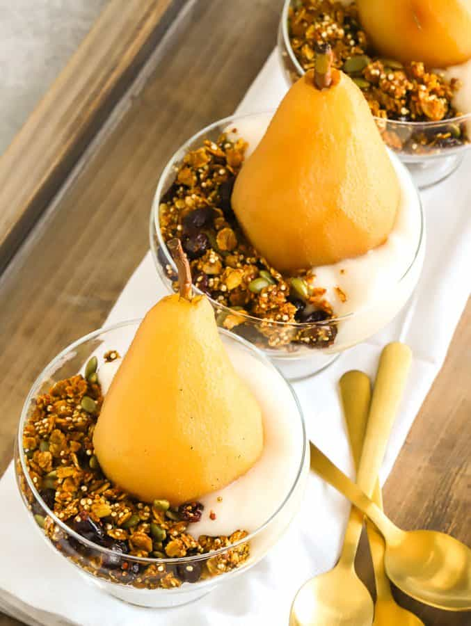 Poached pears with non dairy yogurt, granola for breakfast on wooden tray with gold spoons