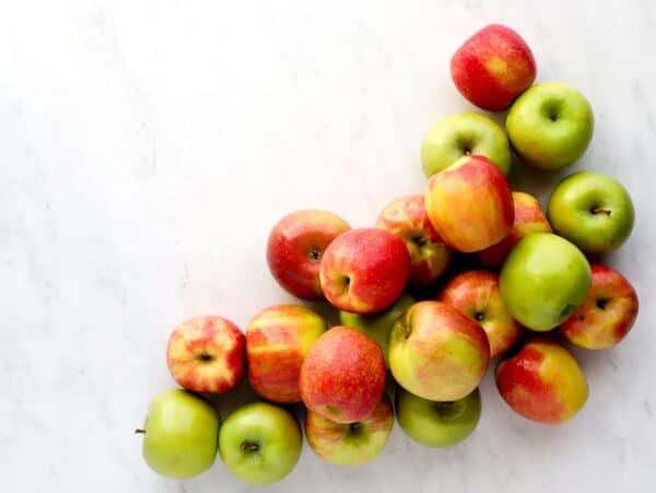 Apples in a pile of honeycrisp, granny smith and pink lady apples