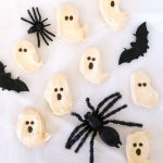 Ghost meringues with chocolate faces and pretend black spiders on a white background