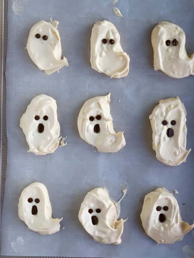 ghost meringues with chocolate faces with two eyes and round mouth