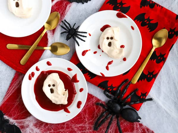 two white plates with ghost meringues with strawberry sauce and splatters