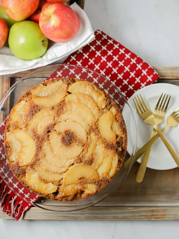 Upside down apple cake on a red kitchen towel with white plates and gold forks