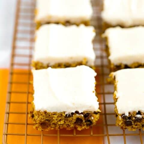 Gluten free pumpkin bars with cream cheese frosting on gold wire baking rack