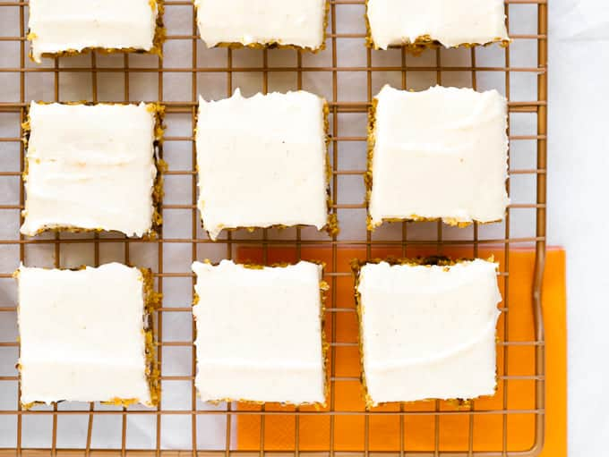 Cream cheese frosted pumpkin bars on wire baking rack