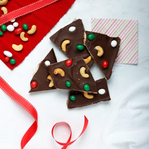 Overhead photo of pieces of cashew bark on white surface with red ribbon