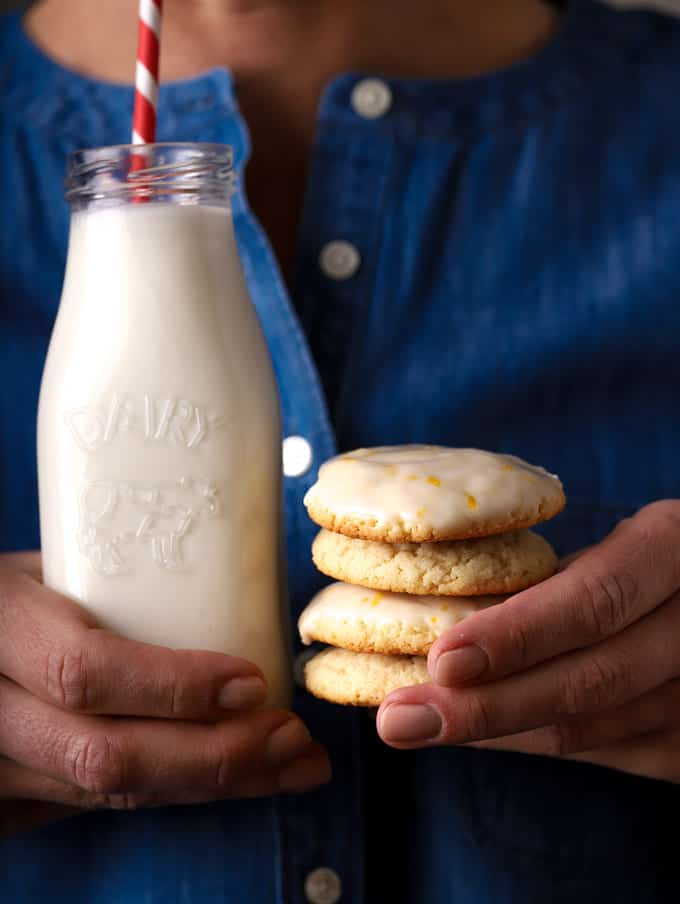 person holding a glass of milk in one hand and stack of cookies in the other hand