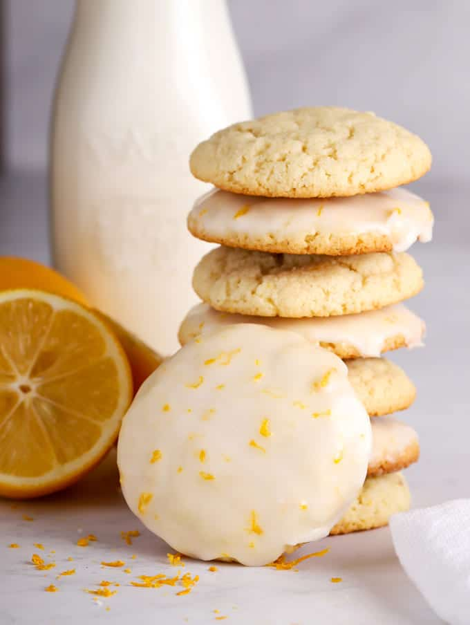 tall stack of lemon cookies with lemon icing glaze and a bottle of milk and a lemon