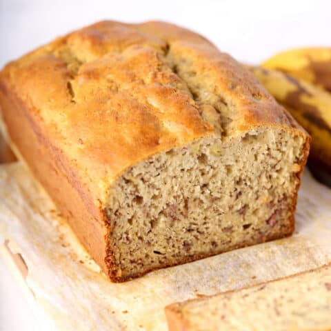 Close up photo of gluten free banana bread on wood cutting board and parchment paper
