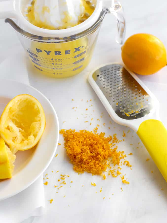 Citrus zester, squeezed meyer lemons and zest on marble board