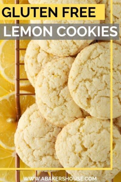 gluten free lemon cookies piled on baking wire rack with lemon slices underneath