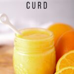 orange curd with white spoon and sliced oranges on cutting board