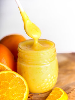 spoon dipping into jar of orange curd