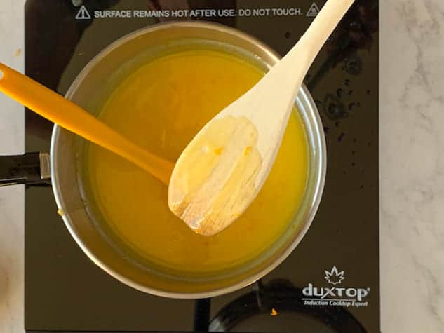 Wooden spoon coated with orange curd