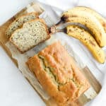 Moist banana bread sliced on cutting board with 3 bananas