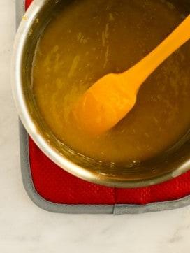 yellow spatula in saucepan of vegan lemon curd