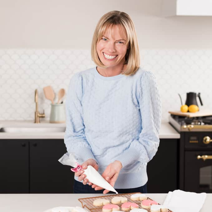 Holly Baker square photo in blue sweater icing cookies in kitchen