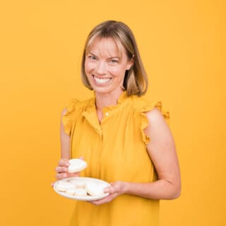 Square photo of Holly Baker with plate of white heart cookies