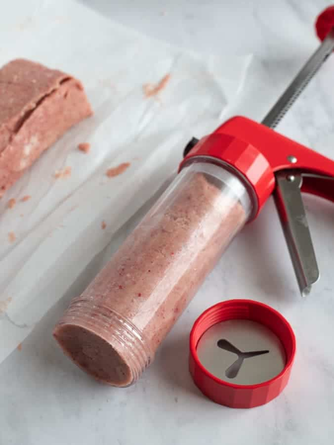 Spritz cookie press with pink cookie dough