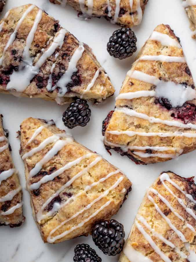 overhead photo of vegan blackberry scones with icing drizzle on marble board