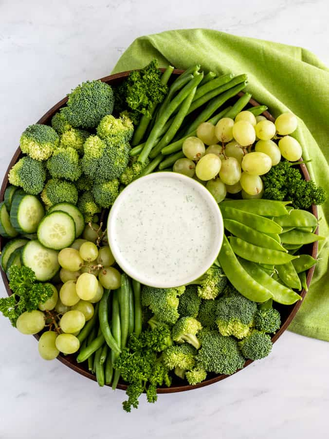 cucumber and feta dip with green napkin and fruits and veggies
