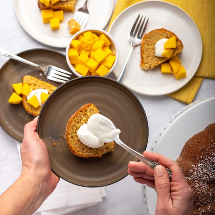 Mango bundt cake on gray plate with hands adding dollop of yogurt