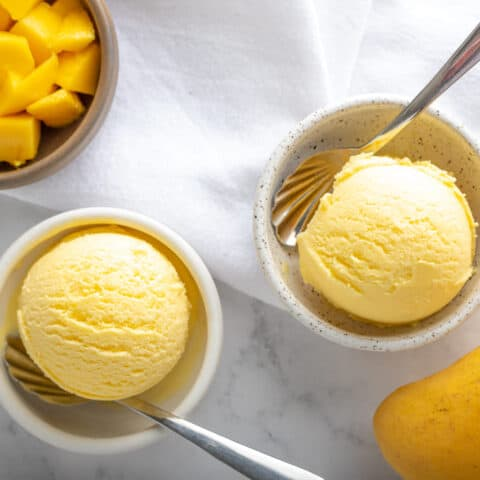 two scoops of mango gelato in two bowls with diced mango