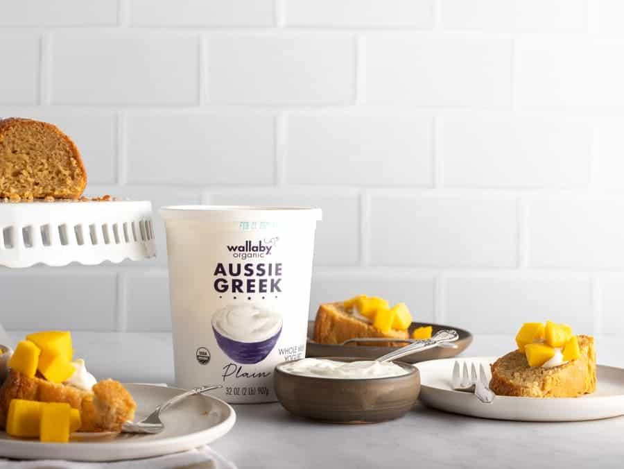 slices of mango cake with carton of wallany greek yogurt