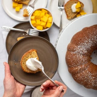 Slice of mango cake with dollop of yogurt and bundt cake in background