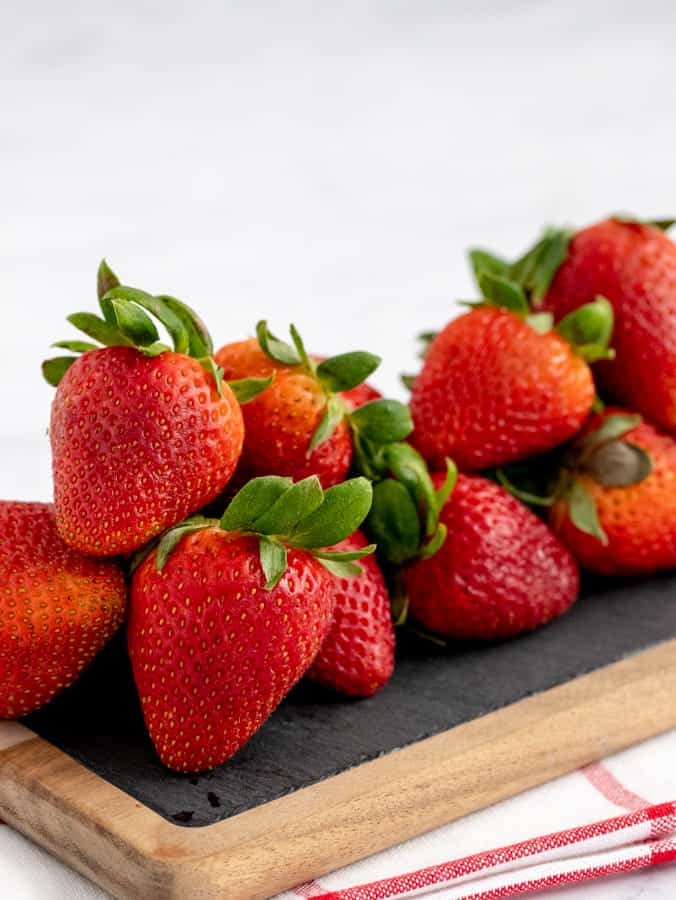 Fresh strawberries on a slate and wooden board with white and red towel underneath