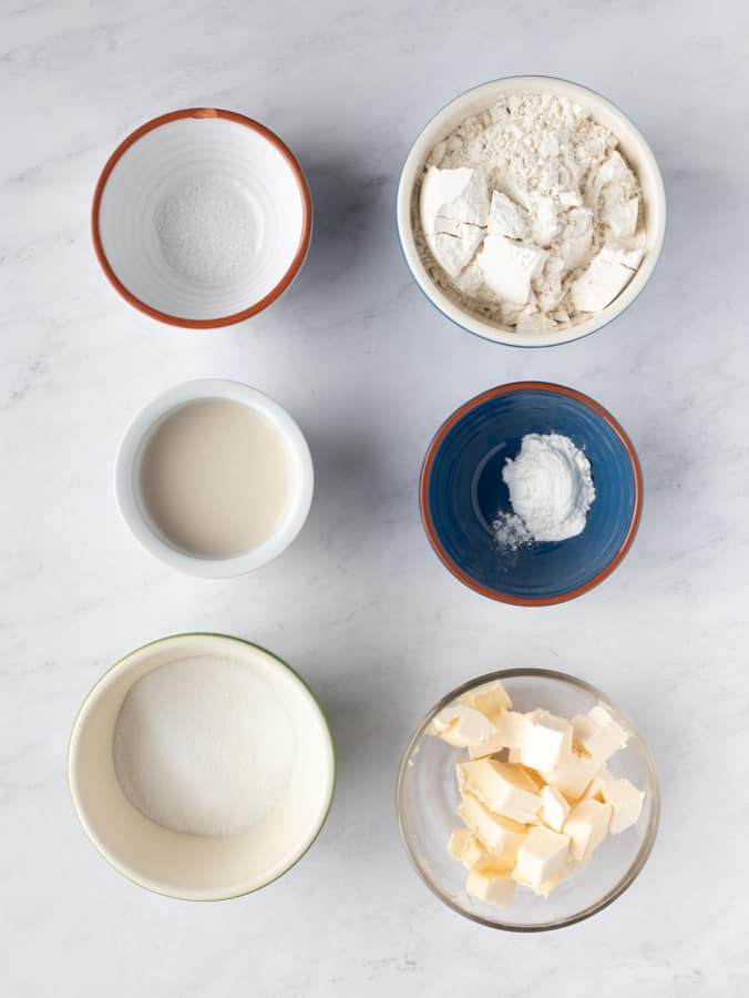 six ingredients in bowls needed to make shortcakes