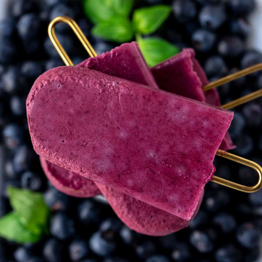 Frozen blueberry popsicles stacked in a group of three with gold handles on top of fresh berries