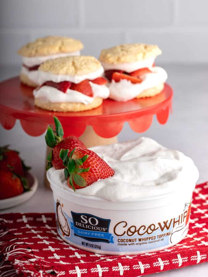 tub of Cocowhip with two strawberries on red and white towel
