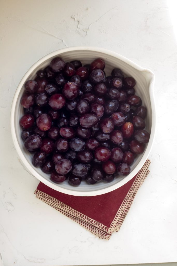 Bowl full of Gum Drop Grapes on a white surface