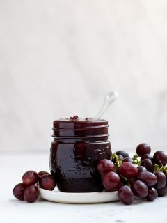 mason jar filled with grape jam with fresh grapes