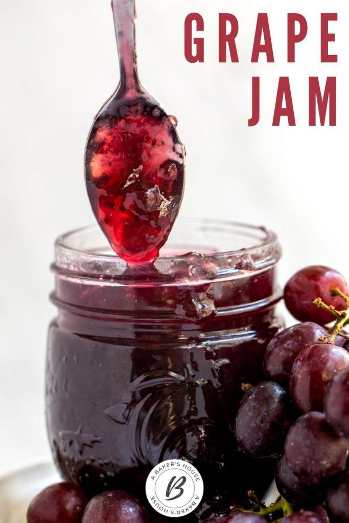 Spoonful of grape jam dipping into mason jar of jam