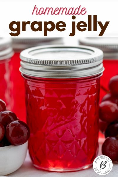 Single jar of grape jelly with silver lid and other jars in background with fresh grapes.