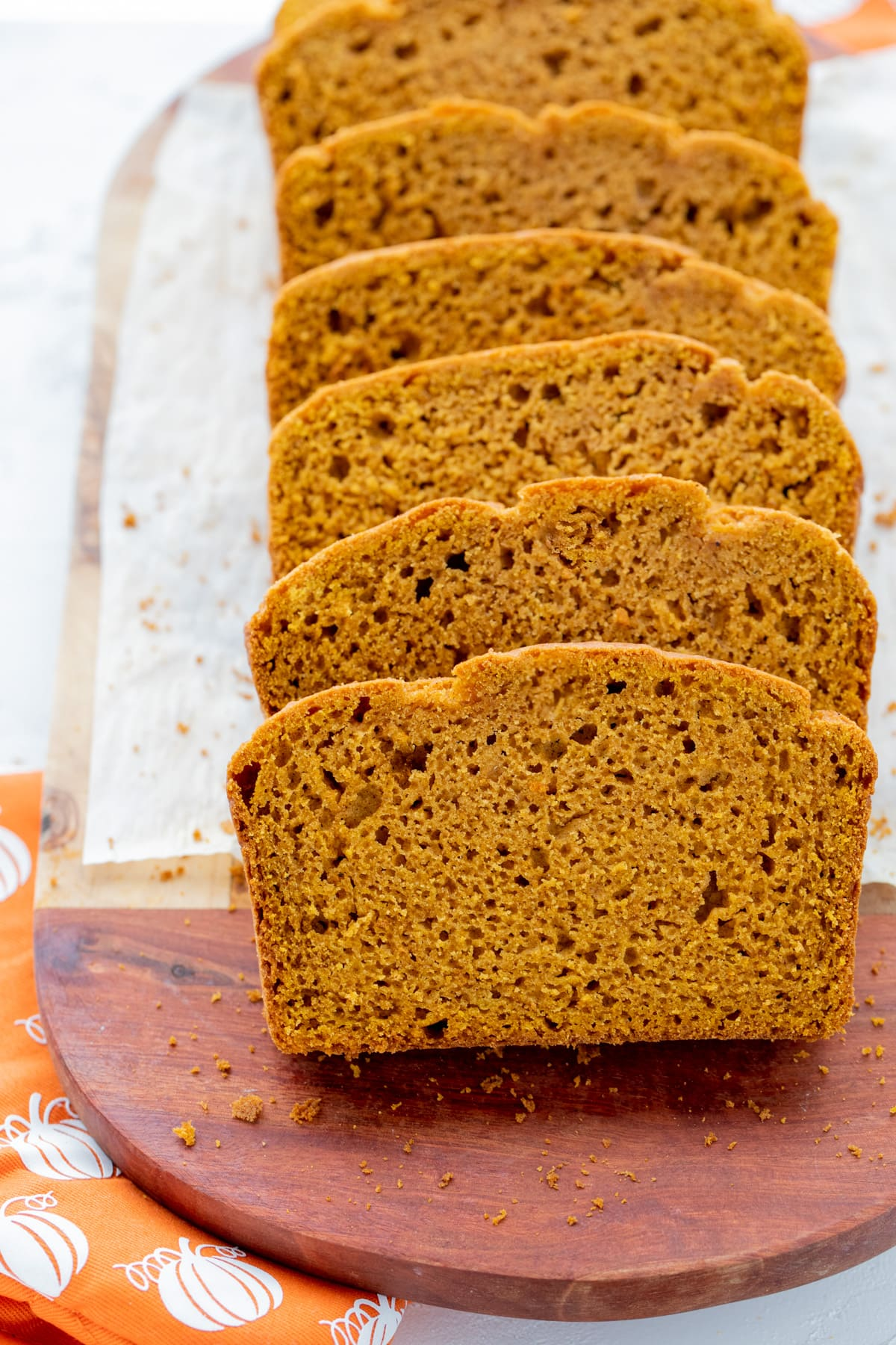 Slices of pumpkin bread on white parchment and wooden cutting board