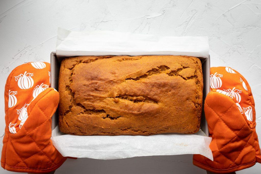 Freshly baked loaf of pumpkin bread in loaf pan held by two pumpkin orange baking mitts