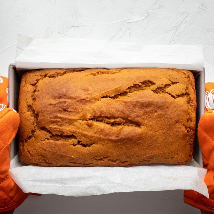 Fresh loaf of pumpkin bread held by two orange pumpkin baking mitts