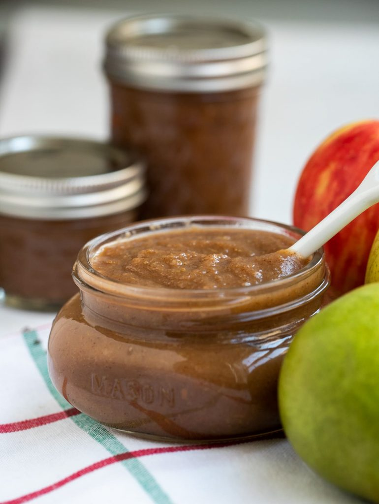 Apple pear butter in a small mason jar on a white towel next to pears and apples