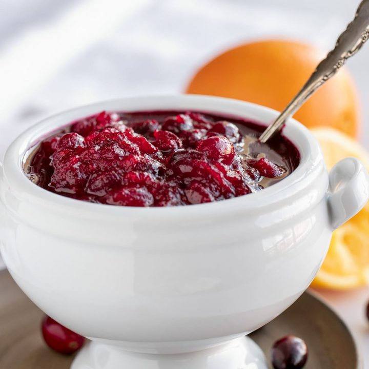 white bowl of cranberry sauce with oranges and silver spoon